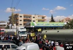 Orang-orang mengibarkan bendera gerakan Syiah Lebanon Hizbullah, saat menyambut kedatangan tanker yang membawa bahan bakar Iran dari Suriah, di kota Baalbeck, lembah Bekaa Lebanon, 16 September 2021.