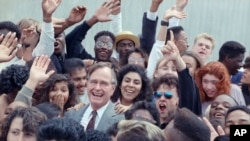 FILE - U.S. President George H.W. Bush is surrounded by cheering students from the Independent Living Program in Los Angeles, as Bush prepared to leave Los Angeles International Airport after presenting a Point of Light award in the area, May 21, 1990.