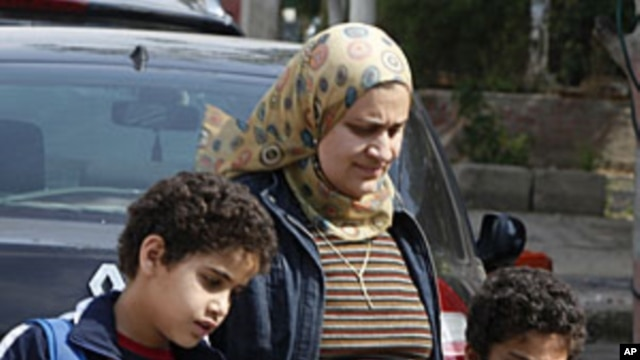 An Egyptian mother collects her sons outside a school in Cairo, April 4, 2011. During the recent mass uprising, as much as fifty percent of police disappeared from cities and their withdrawal has created a security vacuum, letting crime flourish.