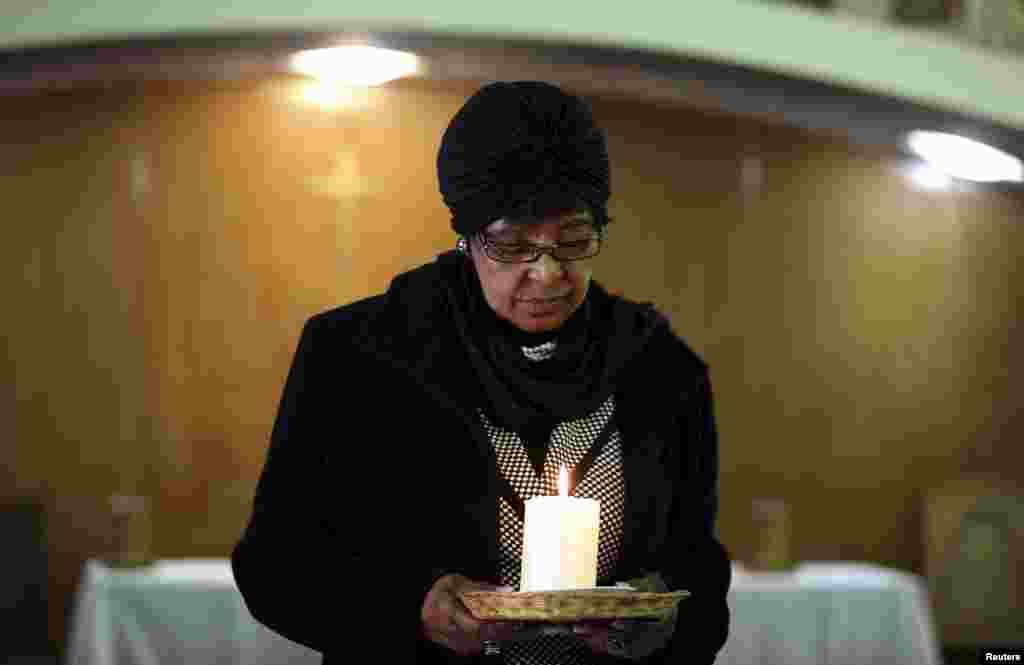 Winnie Madikizela-Mandela, ex-wife of former South African President Nelson Mandela, holds a candle during a prayer service for the ailing Mandela at a church in Johannesburg, July 5, 2013.
