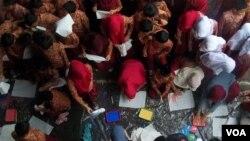 Para murid SDN Andir Kidul Bandung mengecap tangan mereka di atas kain perca integritas. (VOA/R. Teja Wulan)