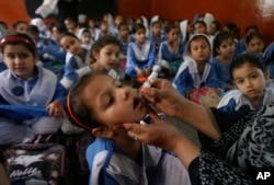 FILE - A health worker gives a polio vaccination to students in Peshawar, Pakistan, April 22, 2019.