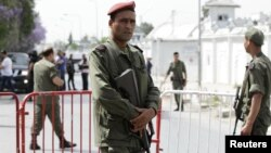 A Tunisian army officer stands guard outside the Bouchoucha military base after shooting in Tunis, Tunisia, May 25, 2015.