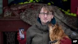 Vaidas Gecevicius, yang mengembangkan aplikasi pengadopsian anjing tak bertuan berpose dengan seekkor anjing dan menunjukkan profile sang anjing dalam sebuah aplikasi GetPet, 2 Februari 2019, Vilnius, Lithuania (foto: AP Photo/Mindaugas Kulbis)