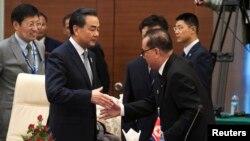 지난해 8월 미얀마 수도 네피도에서 열린 아세안지역안보포럼(ARF)에서 왕이 중국 외교부장(왼쪽)과 리수용 북한 외무상이 악수하고 있다. (자료사진)
