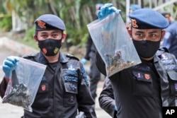 Polisi menunjukkan tas plastik berisi barang bukti yang dikumpulkan dari lokasi ledakan di Gereja Katedral, Makassar, Senin (29/3).