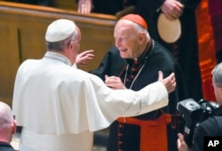 FILE - In this Sept. 23, 2015 file photo, Pope Francis reaches out to hug Cardinal Archbishop emeritus Theodore McCarrick after the Midday Prayer of the Divine with more than 300 U.S. Bishops at the Cathedral of St. Matthew the Apostle in Washington.