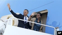 奥巴马总统与第一夫人米歇尔奥巴马在启程前往亚洲时向人们挥手