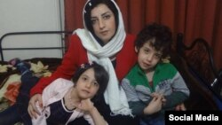 FILE - Narges Mohammadi, an Iranian human rights advocate, who is serving her jail term, is seen along with her two children in their home in Tehran.