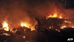 Người biểu tình ném lốp xe vào đống chướng ngại vật đang bốc cháy để ngăn cảnh sát tại Quảng trường Độc lập ở Kiev, ngày 19/2/2014.