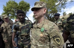 US General Donald C. Bolduc (C) walks on after been awarded with the officer decoration of the National Order of the Lion during the closing ceremony of the three-week joint military exercise between African, US and European troops.