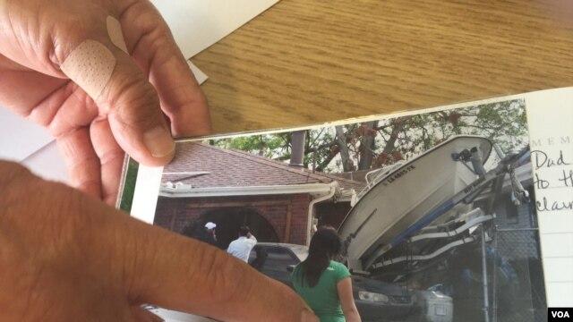 Ông Đỗ Quang Trường chỉ vào một bức hình chụp lại những thiệt hại trước nhà ông sau khi nước rút đi, New Orleans, Louisiana, ngày 29 tháng 8, 2015.