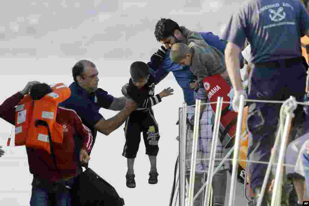 A father passes his son to a coast guard officer (second left), as he disembarks from a vessel at the port of Mitylene after being picked up by the Greek coast guard near the northeast Greek island of Lesvos.