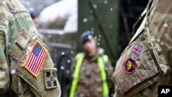 """Un soldat britannique et un soldat américain se tiennent côte à côte après une conférence de presse sur la manœuvre militaire """"Defender 2020"""" à Brueck, en Allemagne, mercredi 26 février 2020."""