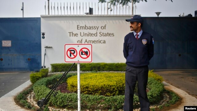 FILE - A private security guard stands outside the U.S. embassy in New Delhi, Dec. 18, 2013.