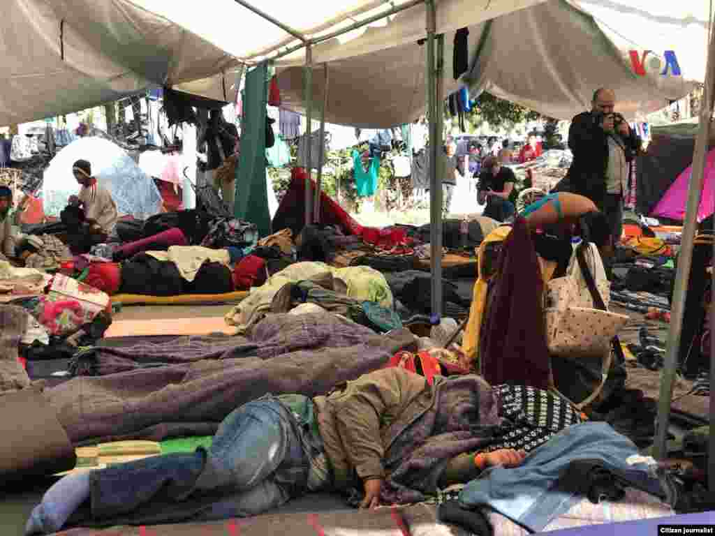 La gente descansa en el piso en un albergue en Tijuana, donde están a la espera de poder entrar a territorio estadounidense. Fotografía: Celia Mendoza- VOA