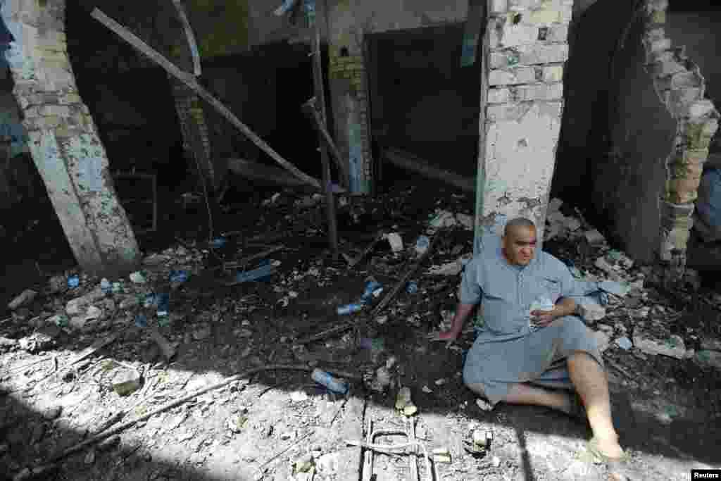 Một người đàn ông ngồi tại địa điểm nơi một cuộc tấn công tự sát xảy ra tại lối vào Lăng Mohammed bin Ali al-Hadi của người Hồi giáo Shia tại thành phố Balad, phía bắc thủ đô Baghdad, Iraq. Những kẻ khủng bố Nhà nước Hồi giáo giết chết ít nhất 35 người và làm bị thương hàng chục người khác vào cuối ngày thứ Năm trong vụ tấn công này.