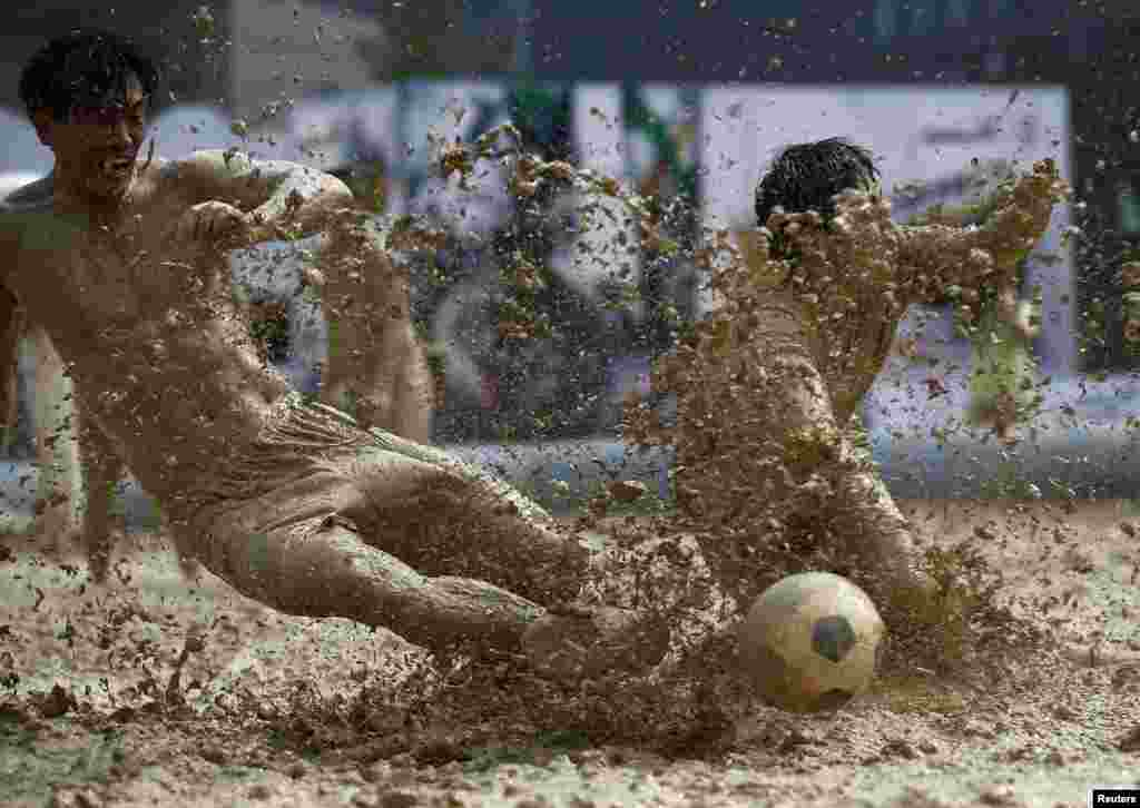 Players battle for the ball during a match at the swamp soccer China tournament in Beijing.