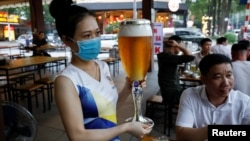 A woman serves beer at a restaurant after the govenment eased nationawide lockdown during the coronavirus disease (COVID-19) outbreak in Hanoi, Vietnam April 29, 2020.