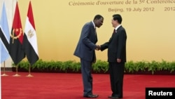 China's President Hu Jintao (R) shakes hand with Benin's President Thomas Yayi Boni before a group photo session during the opening ceremony for the Fifth Forum on China-Africa Cooperation at the Great Hall of the People in Beijing, July 19, 2012.