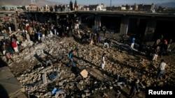 Warga Pakistan memeriksa lokasi ledakan di kawasan warga Syiah di Quetta yang menewaskan sedikitnya 80 orang (16/2).