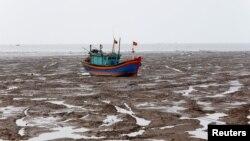 一艘渔船在越南清化省低潮期的海滩上(2018年6月4日)。