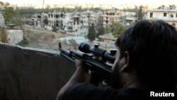 A Free Syrian Army sniper looks through the scope of his rifle at an area controlled by forces loyal to Syria's President Bashar al-Assad in Aleppo' September 11, 2013.Analysts say the FSA lacks effective leadership.