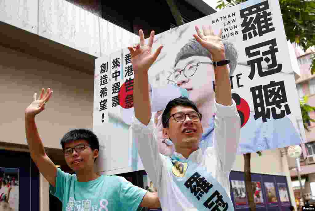 Nathan Law, (R), candidate from Demosisto and student activist Joshua Wong greet supporters on election day for the Legislative Council in Hong Kong, China.