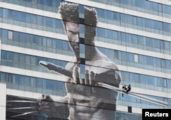 "FILE - A worker installs a poster of Hugh Jackman in the new movie ""The Wolverine"" on a building in Bangkok July 9, 2013."