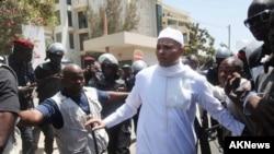 Karim Wade (tengah, kanan) putera mantan Presiden Senegal Abdoulaye Wade, dikelilingi petugas keamanan saat meninggalkan kantor jaksa di Dakar, Senegal, 15 Maret 2015 (Foto: AP Photo)