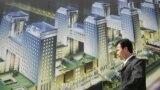 资料照:一名男子走过北京街头张贴的一个新开楼盘的广告牌。