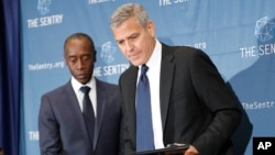 Actors George Clooney, right, and Don Cheadle, left, arrive for a press conference to discuss an investigation about corruption in South Sudan at the National Press Club in Washington, D.C. Sept. 12, 2016.