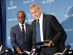 FILE - Actors George Clooney, right, and Don Cheadle, left, arrive for a press conference to discuss an investigation about corruption in South Sudan at the National Press Club in Washington, D.C. Sept. 12, 2016.