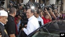 Pemimpin oposisi Malaysia Anwar Ibrahim (tengah) dikerumuni oleh media setibanya di pengadilan tinggi Kuala Lumpur, Malaysia (22/5).