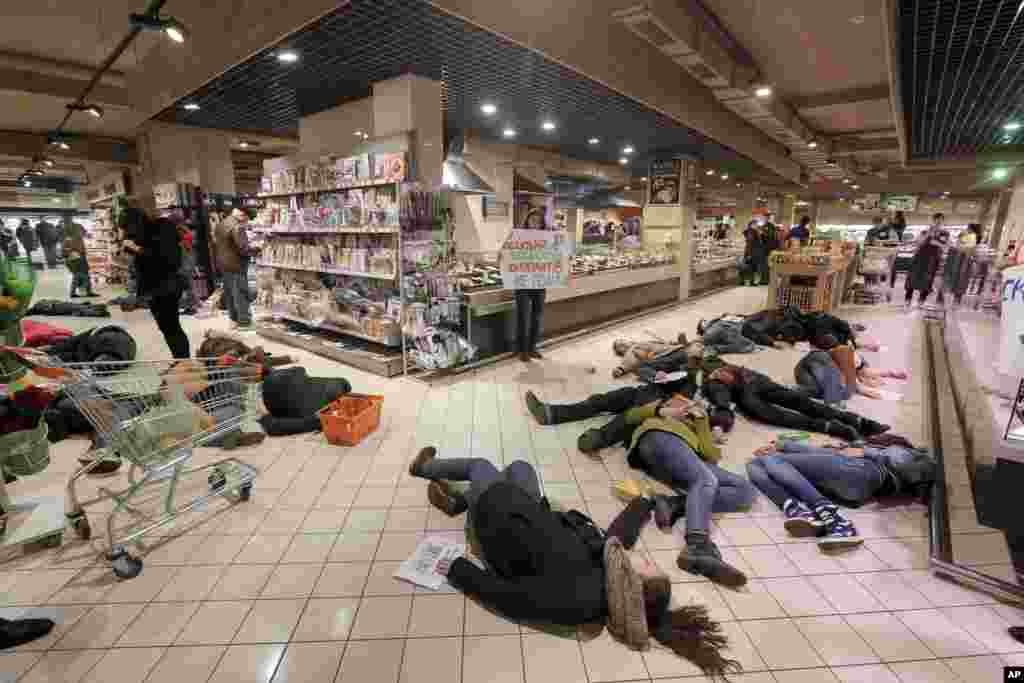 Ukrainians lay on a store's floor, acting as dead bodies in a flash mob action protesting against the buying of  Russian goods in Kyiv.