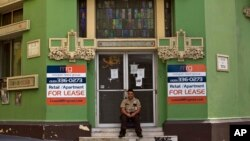 FILE - A private security guard sits in front of a closed down business in the colonial district of Old San Juan, Puerto Rico, Sunday, Aug. 2, 2015. Puerto Rico's government has some $70 billion in debt, $2 billion of which is due Friday.