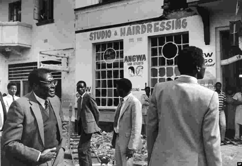 Le Premier ministre du Zimbabwe, Robert Mugabe, est debout dans les décombres à l'extérieur du bâtiment qui abritait le siège du Conseil national africain dans le centre de Harare, après avoir été gravement endommagé par un raid perpétré par des commandos sud-africains, le 19 mai 1986.