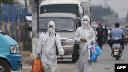 Duas mulheres vestidas com equipamento de proteção junto ao mercado Xinfadi, em Pequim, encerrado devido a novos casos de Covid-19
