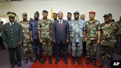 Ivory Coast's President Alassane Ouattara (C) poses with General Philippe Mangou (4L), chief of staff of former pro-Laurent Gbagbo Defense and Security Forces (FDS), and other military officers during a ceremony at the Hotel du Golf in Abidjan on April 12