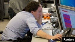A trader looks at his screen on the IG Group trading floor in London March 18, 2013. The surprise decision by eurozone leaders to partially fund a bailout of Cyprus by taxing bank deposits sent shockwaves through financial markets on Monday.
