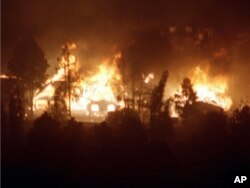 FILE - Homes in west Los Alamos are engulfed in flames as a controlled burn set by the National Park Service last week to clear brush at nearby Bandelier National Monument spread into the town of Los Alamos, May 10, 2000.