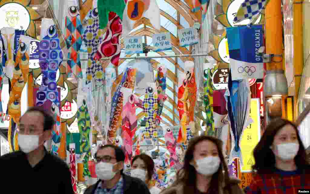 People wearing face masks walk under fluttering Koinobori, traditional Japanese carp-shaped windsocks that are hung in Japan from April to early May to wish a good health for children, following the coronavirus outbreak, in Tokyo, Japan.