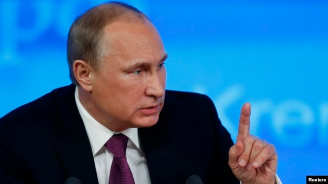 FILE - Russian President Vladimir Putin, shown at a news conference, has signed a revised military doctrine listing NATO and the United States as national security threats.