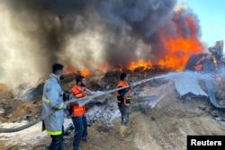 Petugas pemadam kebakaran Palestina memadamkan api di gudang cat yang menurut saksi terkena serangan Israel, di tengah pertempuran Israel-Palestina, di Rafah di Jalur Gaza selatan 18 Mei 2021. (Foto: REUTERS/Bassam Masoud)