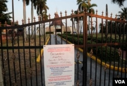 A sign hanging on a locked gate in front of the Ermita de la Caridad church in Miami indicates that the church is closed during the new coronavirus pandemic, Thursday, April 9, 2020.