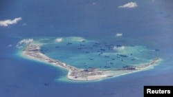 FILE - Chinese dredging vessels are purportedly seen in the waters around Mischief Reef in the disputed Spratly Islands in the South China Sea in this still image from video taken by a P-8A Poseidon surveillance aircraft provided by the U.S. Navy, May 21,