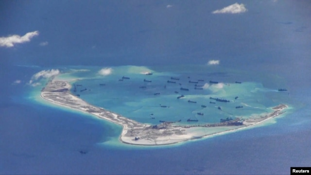 FILE - Chinese dredging vessels are purportedly seen in the waters around Mischief Reef in the disputed Spratly Islands in the South China Sea in this still image taken from video provided by the U.S. Navy, May 21, 2015.