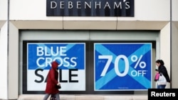 FILE - People walk past a Debenhams store in Stockport, Britain, Jan. 4, 2018.