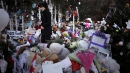 Jeanne Walker walks through an overflowing memorial to the shooting victims, Newtown, Connecticut, December 20, 2012.