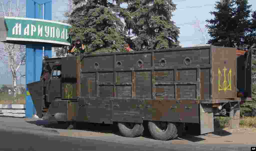 An armored truck with Ukrainian forces guards a checkpoint in the town of Mariupol, eastern Ukraine, Aug. 28, 2014.